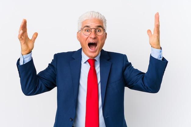 中年の白人ビジネスマンは、嬉しい驚きを受け取り、興奮し、手を挙げて孤立しました。