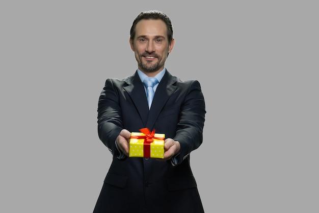カメラにギフトボックスを与える中年の白人ビジネスマン。誰かにギフトボックスを提供する魅力的な男。愛をこめてあなたのために。