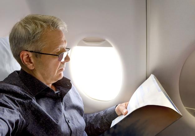 飛行機で旅行中に雑誌を読んでいる中年の白人男性。航空機のキャビン内部