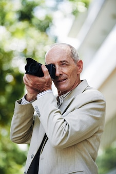 Middle-aged caucasian man taking photos in street with professional digital camera