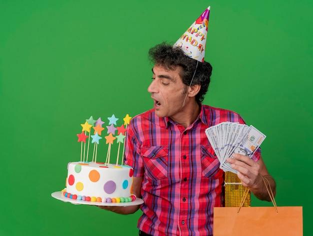 Uomo caucasico di mezza età del partito che indossa il cappello di compleanno che tiene il pacchetto regalo del sacchetto di carta della torta di compleanno e soldi che esaminano la torta che si prepara a morderlo isolato su priorità bassa verde