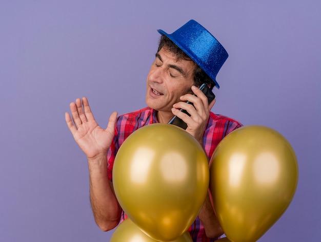 보라색 배경에 고립 된 닫힌 된 눈으로 공기에 손을 유지하는 전화에 얘기하는 풍선 뒤에 서있는 파티 모자를 쓰고 중 년 백인 파티 남자