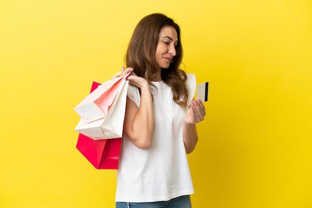 쇼핑백과 신용 카드를 들고 노란색 배경에 고립 된 중년 백인 여성