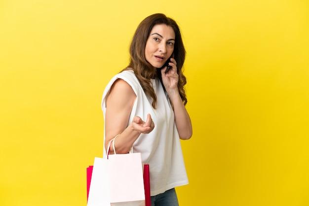 노란색 배경에 격리된 중년 백인 여성이 쇼핑백을 들고 휴대전화로 친구에게 전화를 걸었습니다.