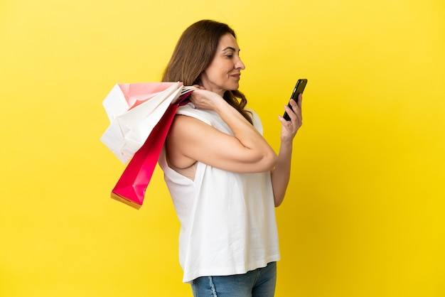 ショッピングバッグを保持し、友人に彼女の携帯電話でメッセージを書いている黄色の背景に分離された中年の白人女性
