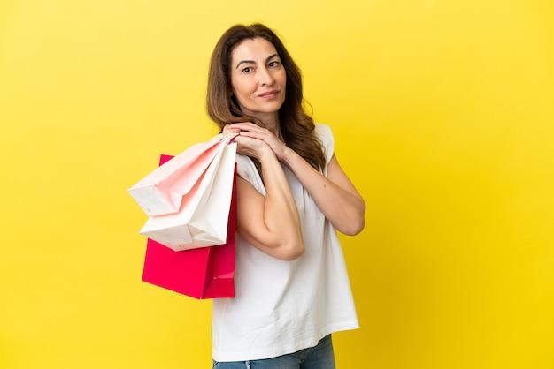 쇼핑백을 들고 노란색 배경에 고립 된 중년 백인 여자