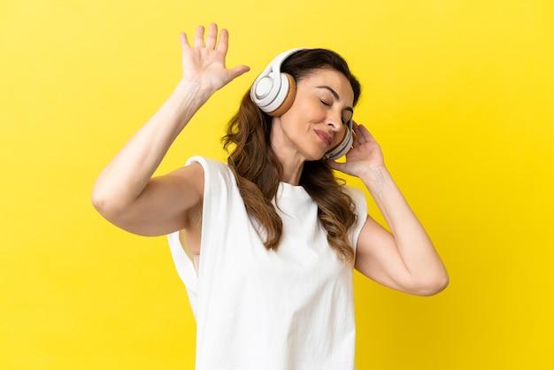 노란색 배경 음악을 듣고 춤을 추는 중년의 백인 여성