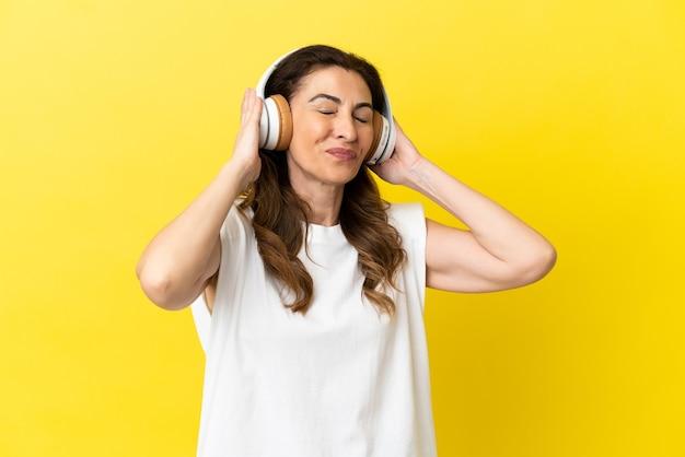 Кавказская женщина средних лет изолирована на желтом фоне, слушает музыку и поет