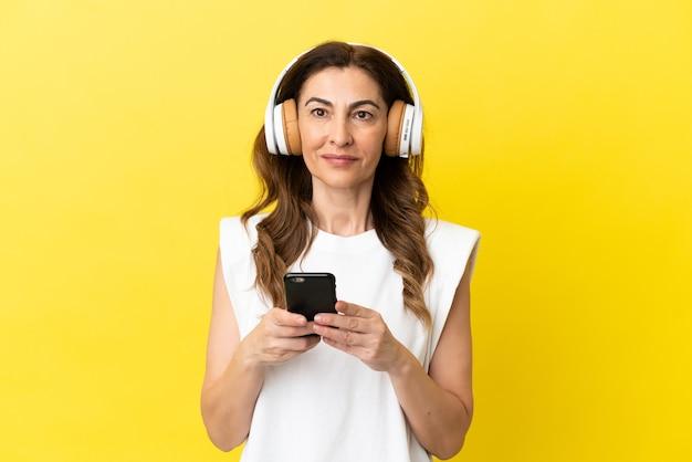 노란색 배경에 격리된 중년의 백인 여성이 휴대폰으로 음악을 듣고 앞을 바라보고 있습니다