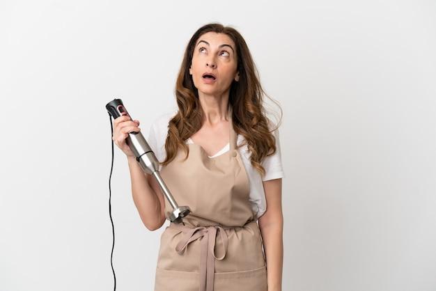 Кавказская женщина средних лет использует ручной блендер, изолированные на белом фоне, глядя вверх и с удивленным выражением лица