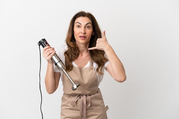 Кавказская женщина средних лет с помощью ручного блендера, изолированного на белом фоне, делая жест телефона. перезвони мне знак