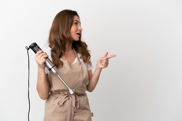 横に指を指し、製品を提示する白い背景で隔離のハンドブレンダーを使用して中年の白人女性