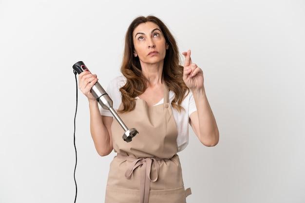 Кавказская женщина средних лет использует ручной блендер, изолированные на белом фоне, скрещивая пальцы и желая всего наилучшего