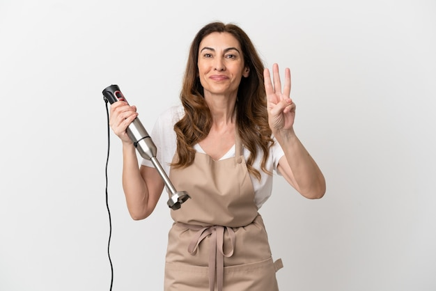 Middle aged caucasian woman using hand blender isolated on white background happy and counting three with fingers