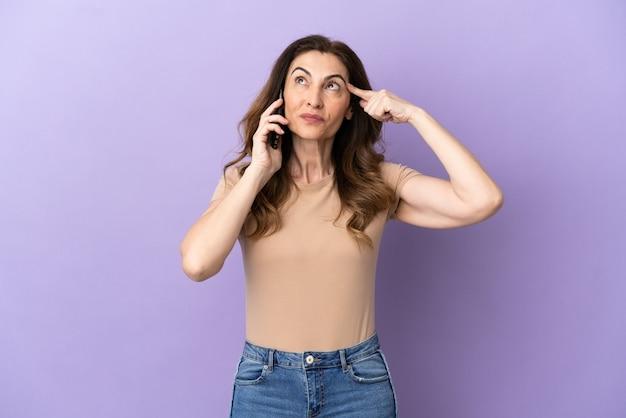 의심과 생각을 가지고 보라색 배경에 고립 된 휴대 전화를 사용하는 중년 백인 여성