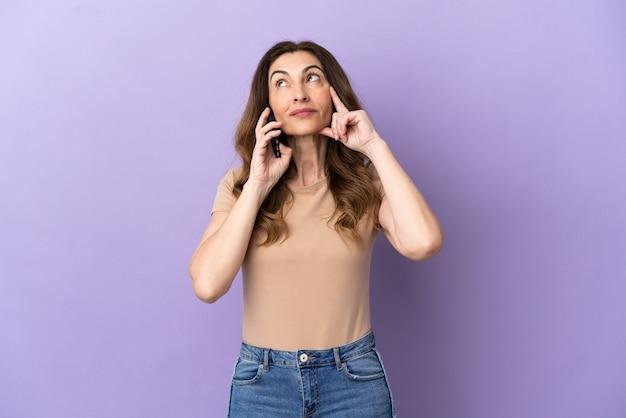 보라색 배경에 격리된 휴대전화를 사용하는 백인 중년 여성은 올려다보는 동안 아이디어를 생각하고 있다