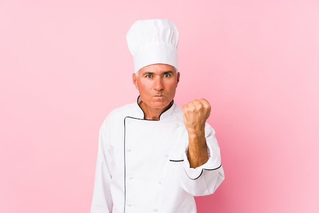 Middle aged cook man isolated , aggressive facial expression.