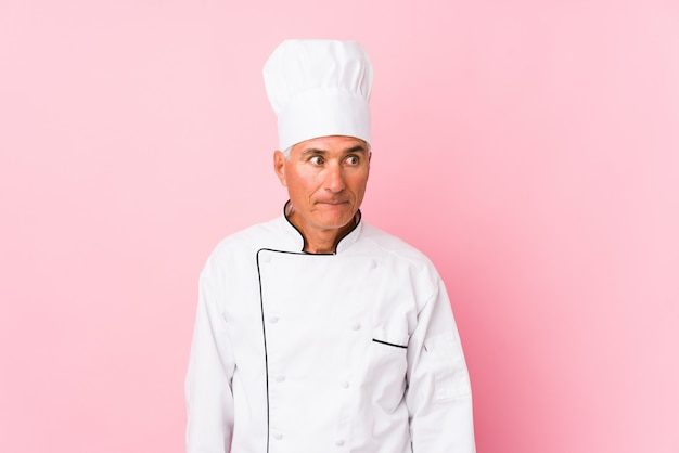 Middle aged cook man isolated confused, feels doubtful and unsure.