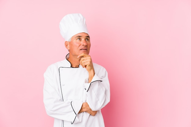 Middle aged cook man isolated looking sideways with doubtful and skeptical expression.