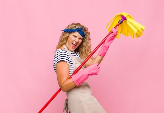 Крутая женщина средних лет со шваброй у розовой стены