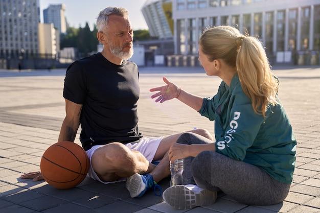 Пара средних лет активный мужчина и женщина в спортивной одежде разговаривают во время отдыха после баскетбола