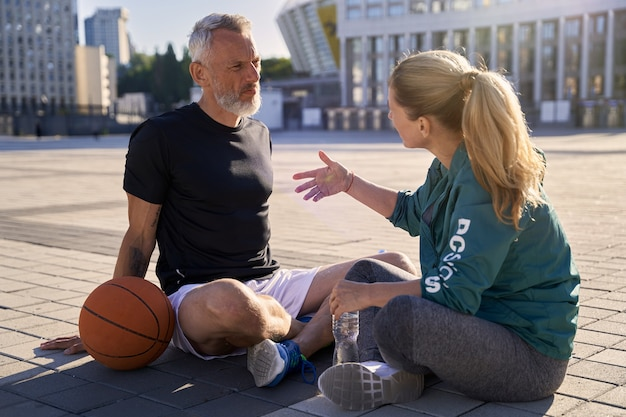 Middle aged couple active man and woman in sportswear talking while relaxing after basketball