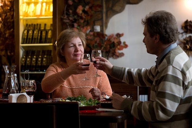 와인을 마시는 중년 부부. 가족이 여가 활동을 하고 레스토랑에서 즐기고 있다
