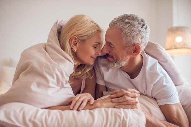Middle-aged couple having romantic moment in bedroom