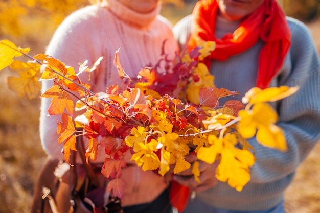 Middle aged couple holding bouquet of autumn branches with yellow and red leaves