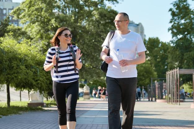 Пожилая пара в спортивной одежде гуляет и разговаривает в парке