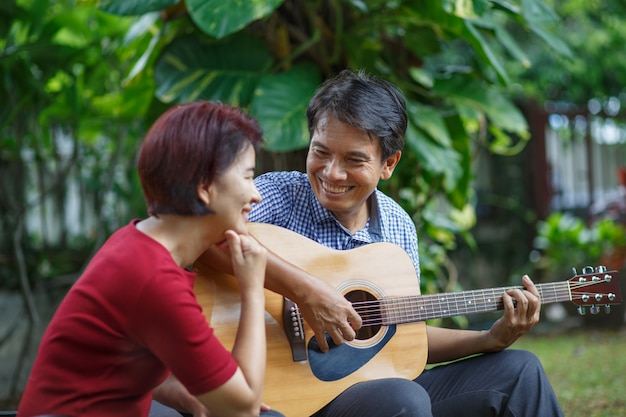 Middle aged  couple playing guitar while relax sitting on bench in backyard.