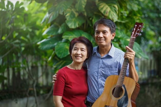 裏庭のベンチに座ってリラックスしながらギターを弾く中年夫婦