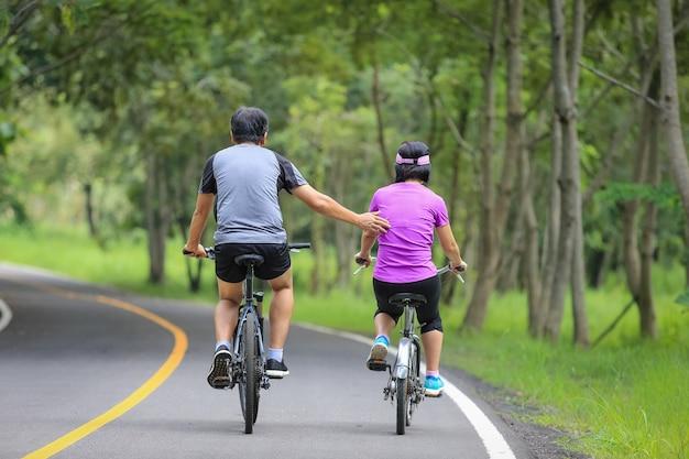 公園で自転車でリラックス運動中年夫婦