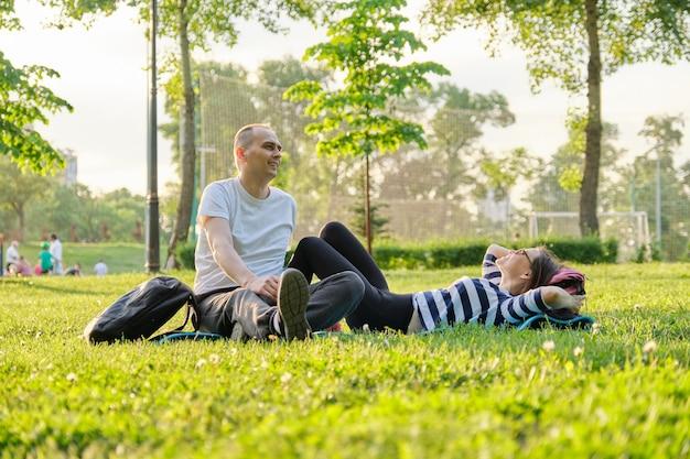 요가 매트에 앉아 있는 중년 부부, 편안한 식수를 이야기하는 남녀. 활동적인 건강한 생활 방식, 관계, 스포츠, 성숙한 사람들의 피트니스