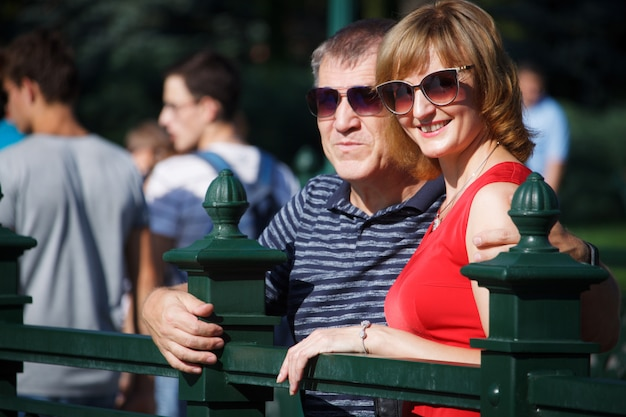 Middle-aged couple smiling and hugging on a walk in a public park, on the background of the fountain, selective focus