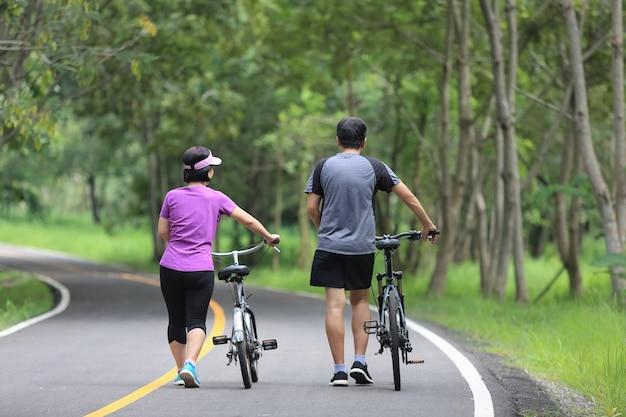 Пара среднего возраста гуляет со своим велосипедом в парке