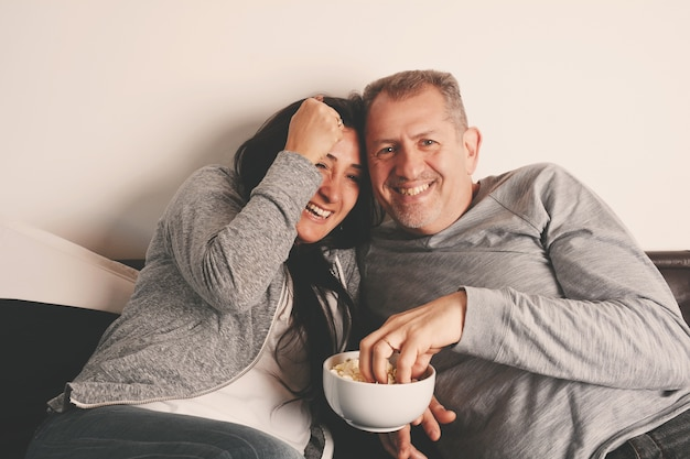Middle aged couple watching movie on tv