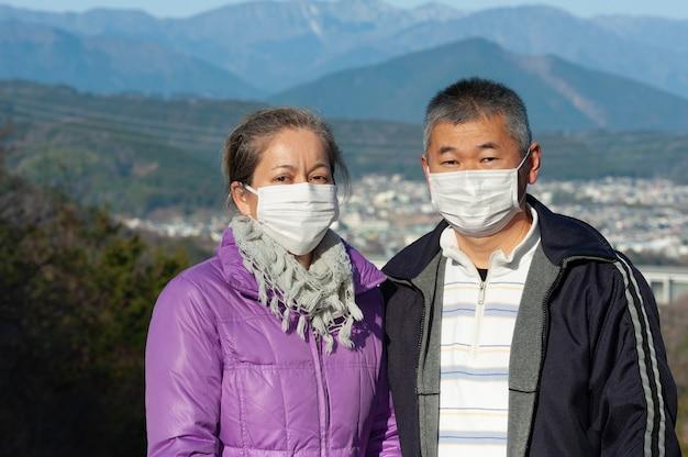 コロナウイルスcovid19からの保護のために白いマスクを身に着けている中年夫婦