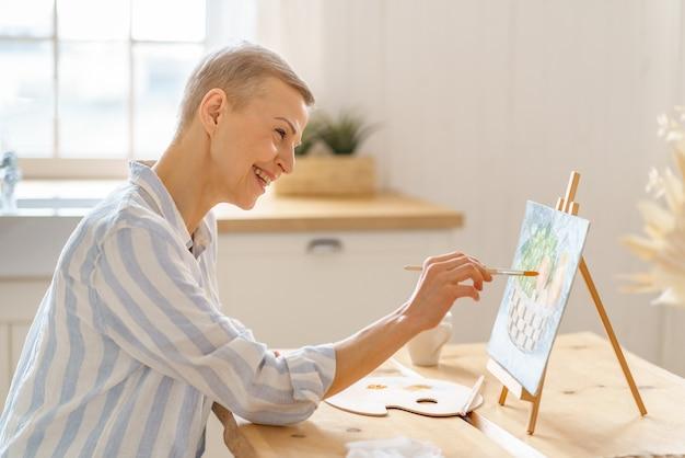 Творческая женщина средних лет рисует картину дома, сидя за деревянным столом на кухне