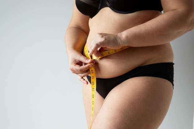 Middle aged curvy woman body measuring her belly