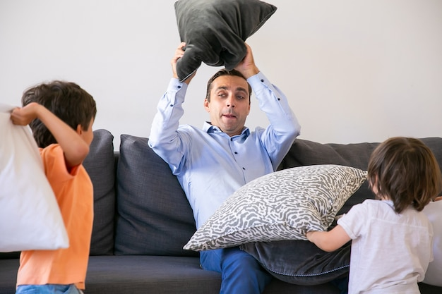 Middle-aged dad playing with kids and fighting with pillows. loving caucasian father sitting on sofa and having fun with two playful sons at home. childhood, weekend and game activity concept