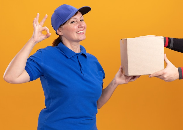 Donna di mezza età delle consegne in uniforme blu e cappuccio che dà la scatola di cartone ad un cliente che sorride amichevole che mostra segno giusto che sta sopra la parete arancione