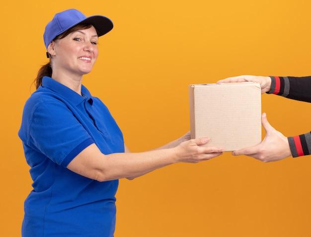 Donna di mezza età delle consegne in uniforme blu e cappuccio che dà la scatola di cartone a un cliente che sorride amichevole che si leva in piedi sopra la parete arancione