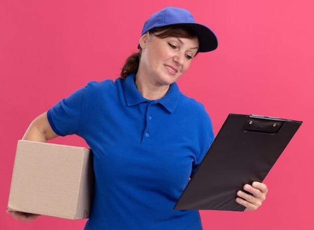 Donna di mezza età delle consegne in uniforme blu e cappuccio che tiene scatola di cartone e appunti guardandolo sorridente in piedi sopra il muro rosa