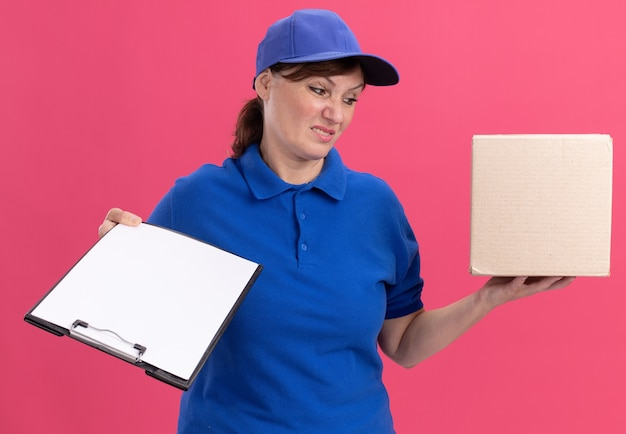 Middle aged delivery woman in blue uniform and cap holding cardboard box and clipboard with blank pages looking confused and displeased standing over pink wall