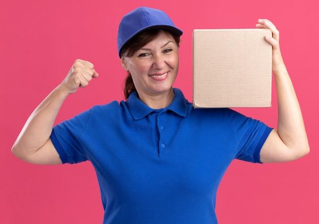 Donna di mezza età delle consegne in uniforme blu e cappuccio che tiene la scatola di cartone che guarda il pugno di serraggio felice ed eccitato davanti che sta sopra il muro rosa