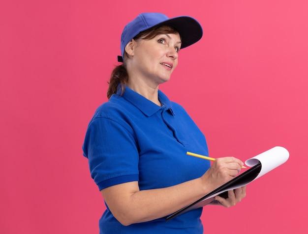 Donna di consegna di mezza età in uniforme blu e cappuccio che tiene appunti e scrittura a matita guardando con espressione pensierosa pensando in piedi sopra la parete rosa