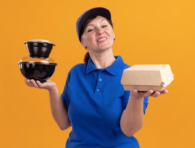 Donna di mezza età delle consegne in uniforme blu e cappuccio che tiene i pacchetti di cibo guardando davanti sorridente felice e positivo in piedi sopra la parete arancione