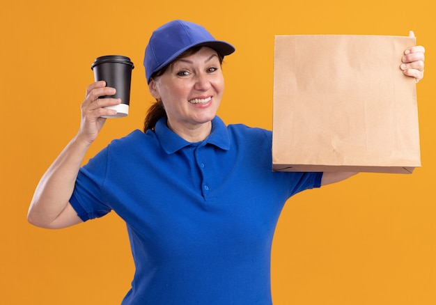 Middle aged delivery woman in blue uniform and cap holding paper package showing coffee cup looking at front smiling cheerfully standing over orange wall