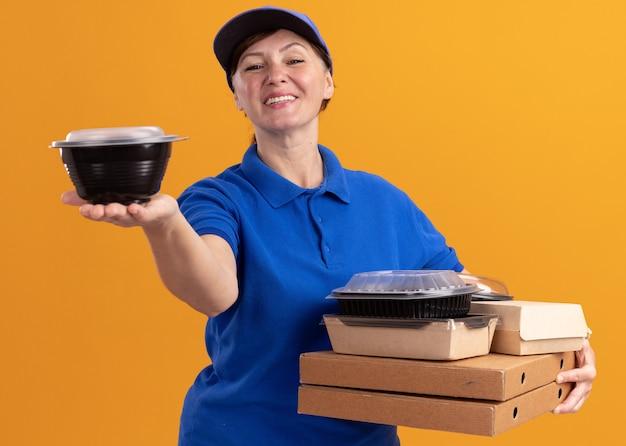 Donna di consegna di mezza età in uniforme blu e cappuccio che tiene scatole per pizza e confezioni di cibo guardando davanti sorridente fiducioso in piedi sopra la parete arancione